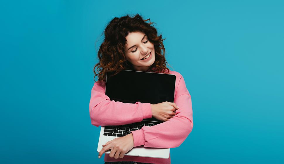 Ragazza che abbraccia un computer portatile felice dell'assistenza